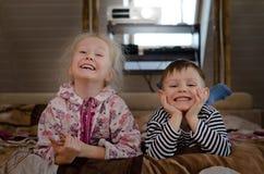 Junger Bruder und Schwester, die zusammen auf einem Bett liegt Lizenzfreies Stockfoto