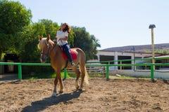 Junger Brunette auf einem braun-blonden Pferd im Reitverein Stockbilder