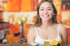 Junger Brunette, der durch Tabelle mit Glas des Honigs, des Granolas und der geschnittenen Zitrone in der Front, glücklich lächel Stockfotografie