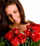 Junger Brunette, der ihre Rosen bewundert Stockbild