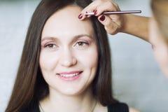 Junger Brunette, der Make-up tut lizenzfreies stockfoto