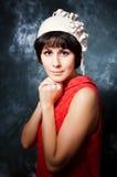 Junger Brunette, der rotes Kleid und Weißfilz trägt Stockbilder