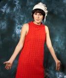 Junger Brunette, der rotes Kleid und Weißfilz trägt Lizenzfreies Stockfoto