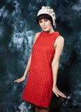 Junger Brunette, der rotes Kleid und Weißfilz trägt Lizenzfreies Stockbild