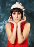 Junger Brunette, der rotes Kleid und Weißfilz trägt Lizenzfreie Stockfotografie