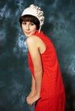 Junger Brunette, der rotes Kleid und Weißfilz trägt Lizenzfreie Stockbilder
