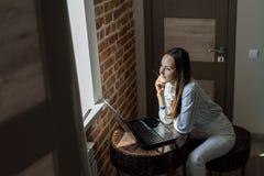 Junger Brunette, der vor einem Laptop am Tisch im Raum sitzt stockfotos
