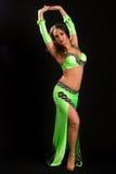 Junger Brunette in einem orientalischen Tanz der grünen Klage lizenzfreie stockbilder