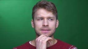 Junger brunette Geschäftsmann, der durchdacht in die Vereinbarung konzentriert wird auf grünen Hintergrund nickt stock video footage