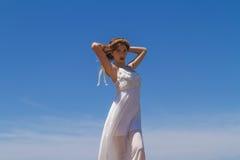 Junger Brunette im weißen schwachen Kleid genießt stockfoto