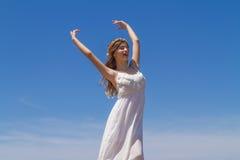 Junger Brunette im weißen schwachen Kleid genießt lizenzfreies stockfoto
