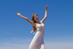 Junger Brunette im weißen schwachen Kleid genießt stockfotografie
