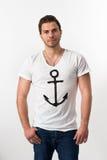 Junger Brunette Mann mit Anker-T-Shirt lizenzfreie stockfotografie