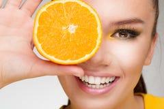 Junger Brunette mit Orange in ihrer Hand Lizenzfreie Stockfotografie