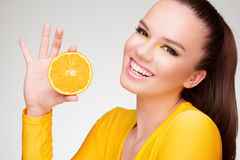 Junger Brunette mit Orange in ihrer Hand stockfotos