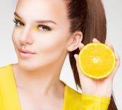 Junger Brunette mit Orange in ihrer Hand Lizenzfreie Stockbilder
