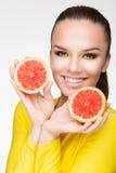 Junger Brunette mit roter Pampelmuse in ihrer Hand Lizenzfreie Stockfotos
