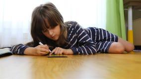 Junger Brunette zeichnet leidenschaftlich das Lügen auf dem Boden stock footage