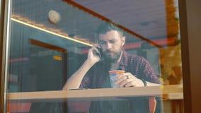 Junger Brunettekerl nennt im Café am Fenster und in trinkendem Kaffee stock video