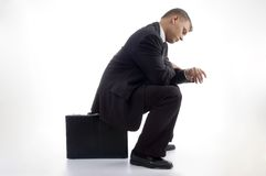 Junger Buchhalter, der einen Blick an seiner Uhr hat Lizenzfreie Stockbilder