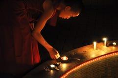 Junger buddhistischer Mönch, der Kerzen beleuchtet Lizenzfreie Stockfotos