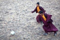 Junger buddhistischer Mönch zwei, der Fußball spielt Stockfotos
