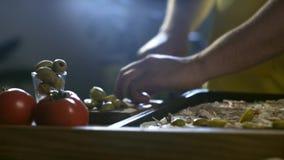 Junger Chef schnitt Oliven auf Tabelle für Pizza 4K stock footage