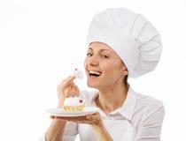 Junger Chefkoch, der einen Kuchen schmeckt Stockbild