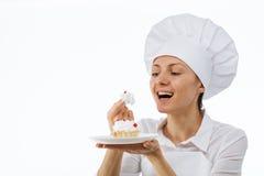 Junger Chefkoch, der einen Kuchen schmeckt Stockbilder