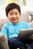 Junger chinesischer Junge, der Tablette-Computer verwendet Stockbild