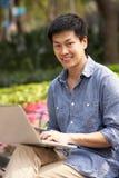 Junger chinesischer Mann, der Laptop verwendet, während entspannend lizenzfreie stockfotos