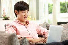 Junger chinesischer Mann, der Laptop verwendet, während entspannend Stockfotografie