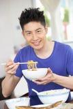 Junger chinesischer Mann, der zu Hause sitzt, Mahlzeit essend Stockfotos