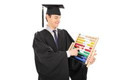 Junger Collegeabsolvent, der auf einem Abakus zählt Stockfotos