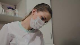 Junger Cosmetologist bei der Arbeit, Porträt eines schönen Cosmetologist in der Maske stock video