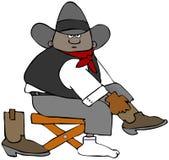Junger Cowboy, der auf seine Stiefel zieht Lizenzfreies Stockbild