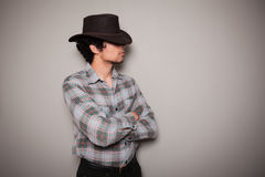 Junger Cowboy im karierten Hemd gegen eine grüne Wand Lizenzfreie Stockfotografie