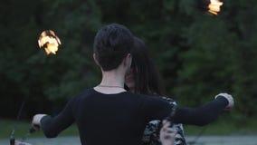 Junger dünner Mann in der schwarzen Kleidung und attraktive Frau führen Show mit Flamme draußen durch Talentierte fireshow Künstl stock footage