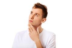 Junger denkender Mann schaut oben mit der Hand nahe Gesicht Stockfotografie