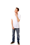 Junger denkender Mann schaut oben mit der Hand nahe Gesicht Lizenzfreies Stockbild