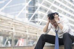 Junger deprimierter Geschäftsmann, der auf der Treppe sitzt Lizenzfreie Stockfotos