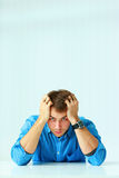 Junger deprimierter Geschäftsmann, der am Tisch sitzt und Kamera betrachtet Lizenzfreie Stockfotos