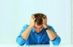 Junger deprimierter Geschäftsmann, der am Tisch sitzt und unten schaut Stockbild