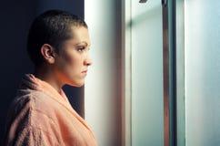 Junger deprimierter Krebspatient vor Krankenhausfenster Stockbilder