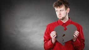 Junger deprimierter Mann abgedeckt durch defektes Herz Stockfotos