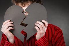 Junger deprimierter Mann abgedeckt durch defektes Herz Stockbild