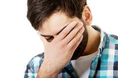 Junger deprimierter Mann, der sein Gesicht berührt Stockfotos