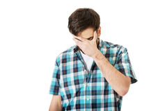 Junger deprimierter Mann, der sein Gesicht berührt Lizenzfreie Stockbilder