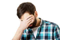 Junger deprimierter Mann, der sein Gesicht berührt Lizenzfreies Stockbild