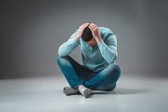 Junger deprimierter Mann, der seinen Kopf mit beiden Händen halten sitzt Stockfotografie